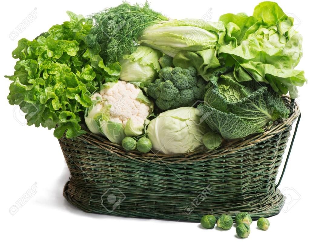 Fresh green vegetables in wicker basket isolated on white